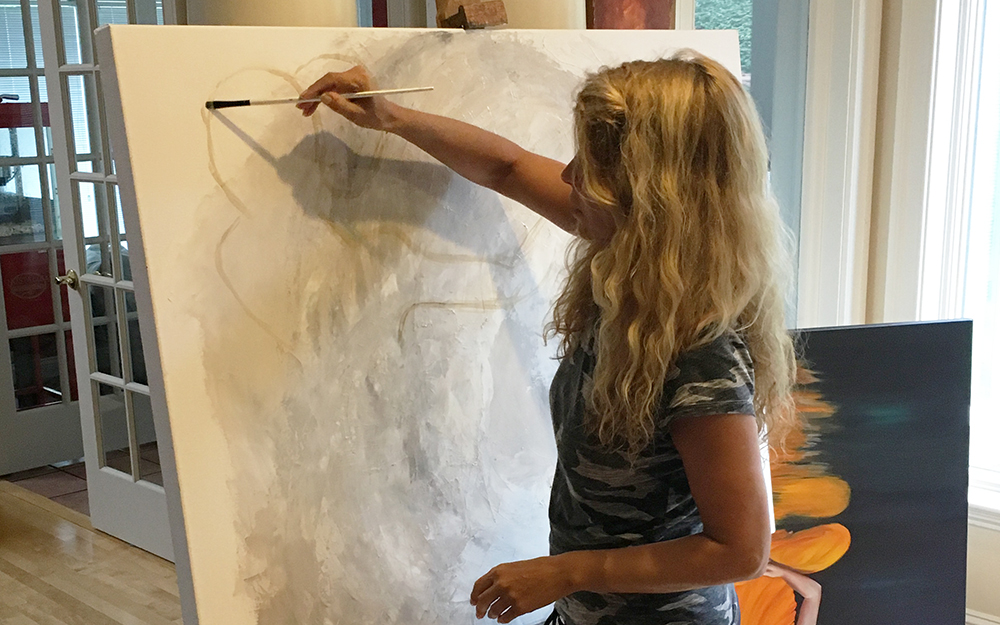 Natalie painting on a blank canvas