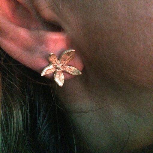 Flower power silver stud earrings on ear