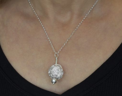 Ball of silver pendant on a neck
